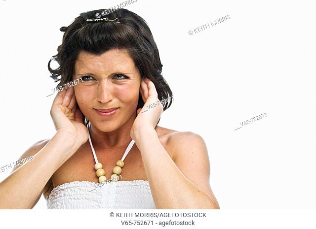 young woman putting her fingers in her ears to reduce the noise around her - suffering from tinitus or noise pollution