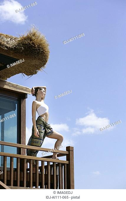 View of a woman standing in wooden balcony