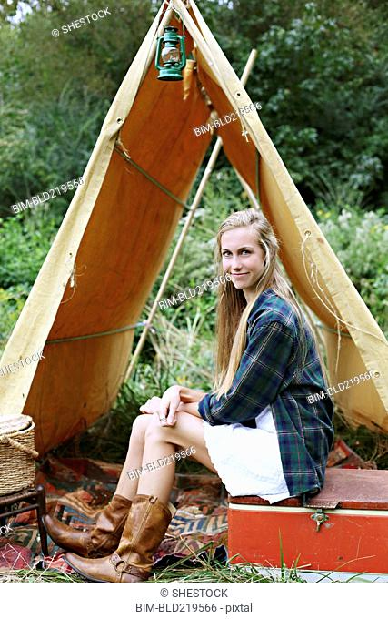 Woman sitting on cooler at camping tent