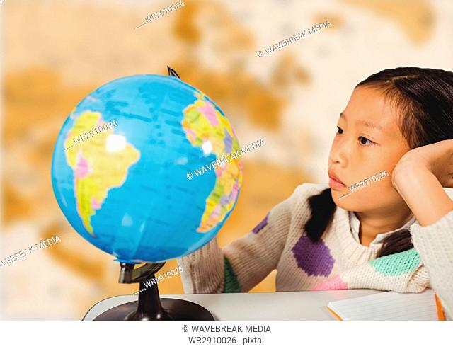 Girl at desk with globe against blurry brown map
