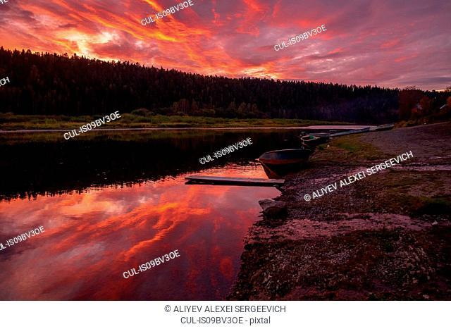 Tree lined river with red orange sky, Ural, Sverdlovsk, Russia