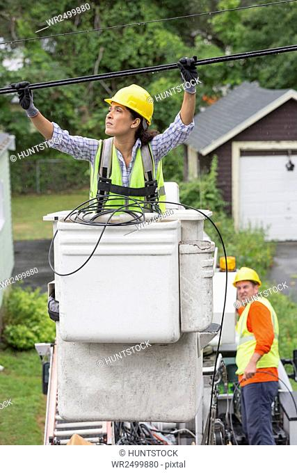 Hispanic female cable lineman examining the cables in the rain
