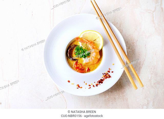 White plate with Spicy Thai soup Tom Yam with Coconut milk, Chili pepper and Shrimp over white marble as background. With wooden chopsticks. Top view