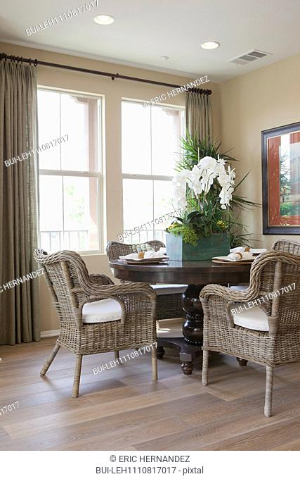 Wicker chairs around dining table by window at home