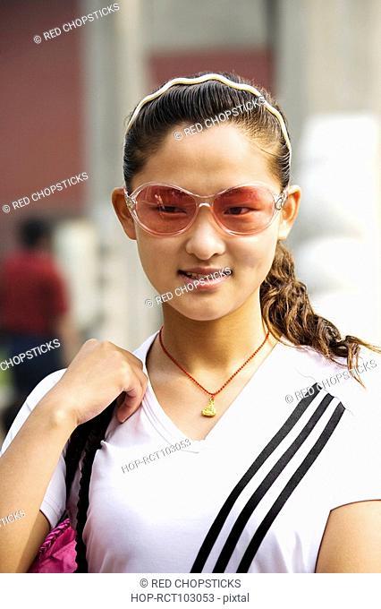 Close-up of a young woman wearing sunglasses, Qufu, Shandong Province, China