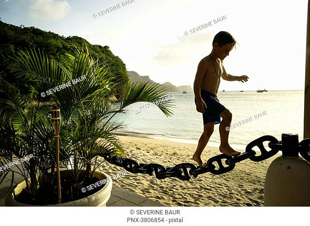A kid of 7 years old is climbing on a chain, Bequia, Saint-Vincent and the Grenadines, West Indies