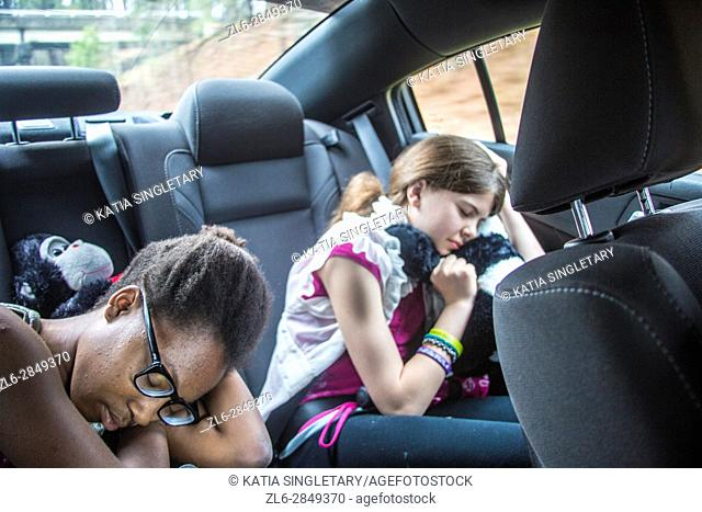 2 girls, one caucasian preteen and one african american teen in the car sleeping and resting with stuff animals and earphones on