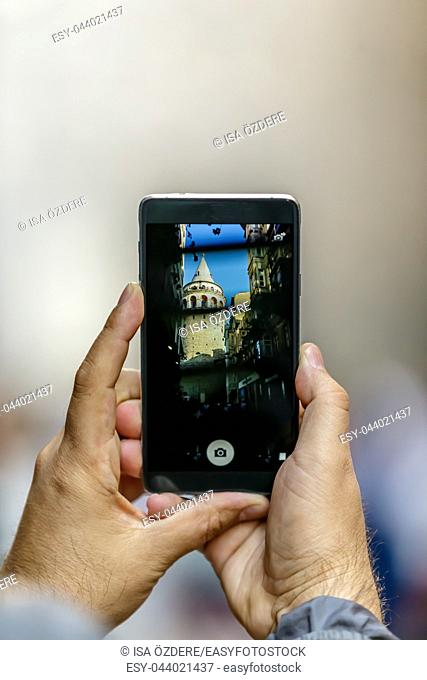Unidentified man takes picture of Galata Tower, a medieval famous landmark stone tower architecture, in Beyoglu, Istanbul