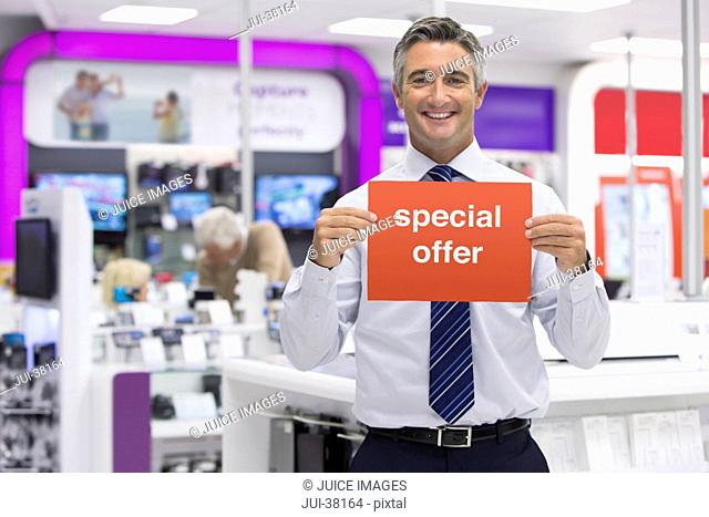 Portrait of smiling salesman holding Special Offer sign in electronics store