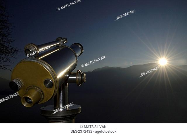 Sun Rays Shine Over The Mountains In The Distance With Binoculars In The Foreground; Ascona, Ticino, Switzerland