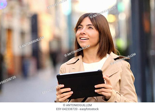 Tourist walking and consulting a guide in a tablet and watching amazed the street