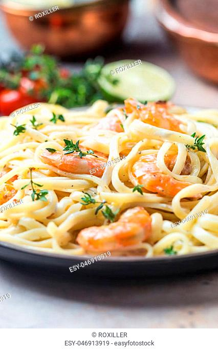 Italian pasta fettuccine in a creamy sauce with shrimp on a plate, close-up