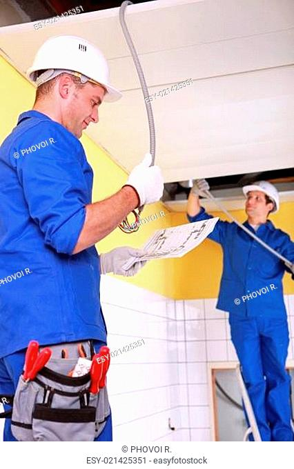 Electricians installing electrical cabling