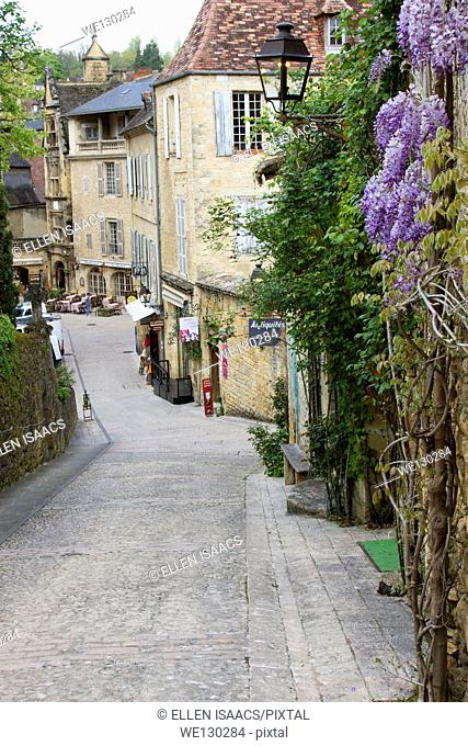 Charming cobblestone street lined with tourist shops slopes down in Sarlat, Dordogne region of France
