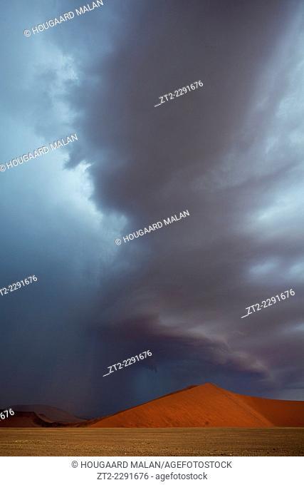 Landscape photo of a big rainstorm over the dunes of Sossusvlei. Sossusvlei, Namib Naukluft National Park, Namibia