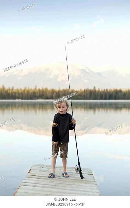Caucasian boy standing on dock at lake holding fishing rod