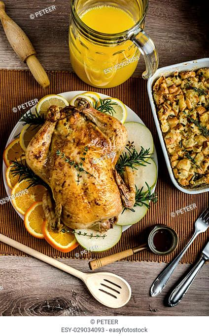 Feasting - stuffed roast chicken with herbs, mashed potatoes with oregano leaves and homemade stuffing with herbs, freshly squeezed orange juice
