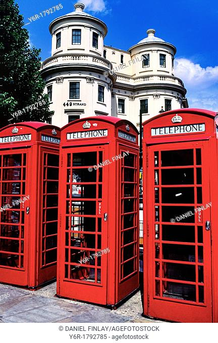 Colorful red telephone boxes in The Strand in sunny London, England, against a background of J  Nash architecture and blue skies