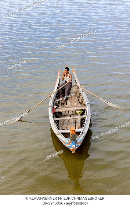 Man in a traditional rowing boat on the Taungthaman Lake, Amarapura, Mandalay Division, Myanmar