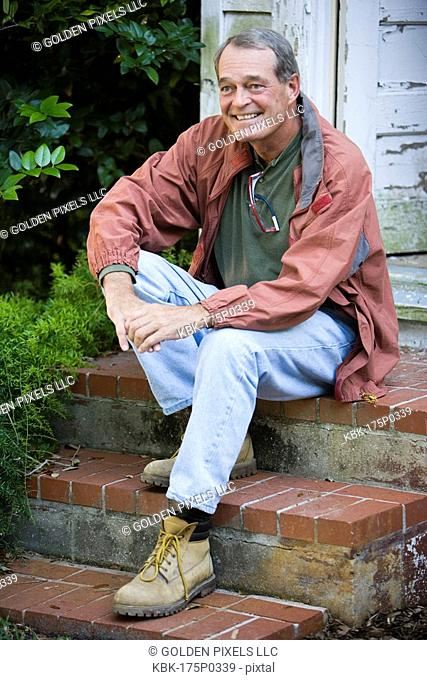 Mature man sitting on doorstep