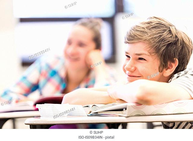 Teenage boy listening at desk in high school lesson