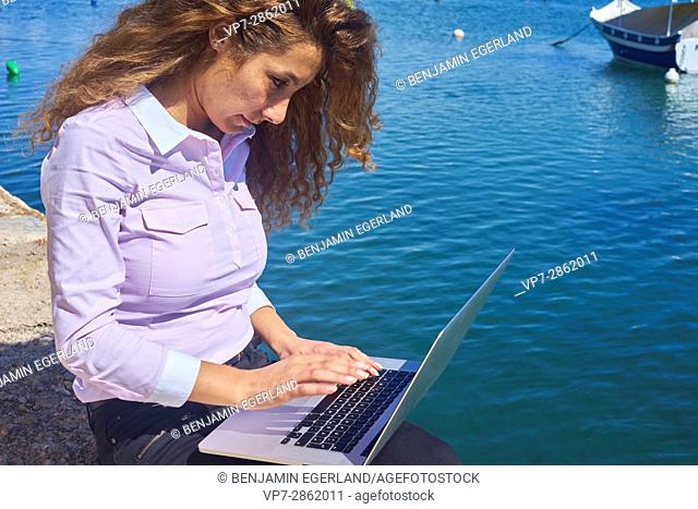 digital nomad - mature business woman working with notebook computer next to sea in holiday destination Malta