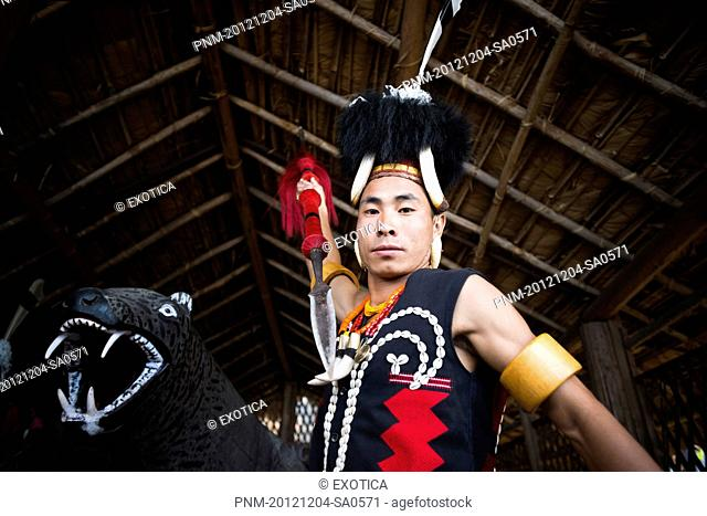 Naga tribal warrior in traditional outfit attacking with a spear, Hornbill Festival, Kohima, Nagaland, India