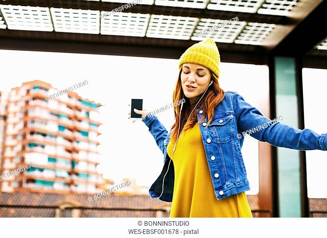 Young woman with yellow cap dancing while listening music with earphones