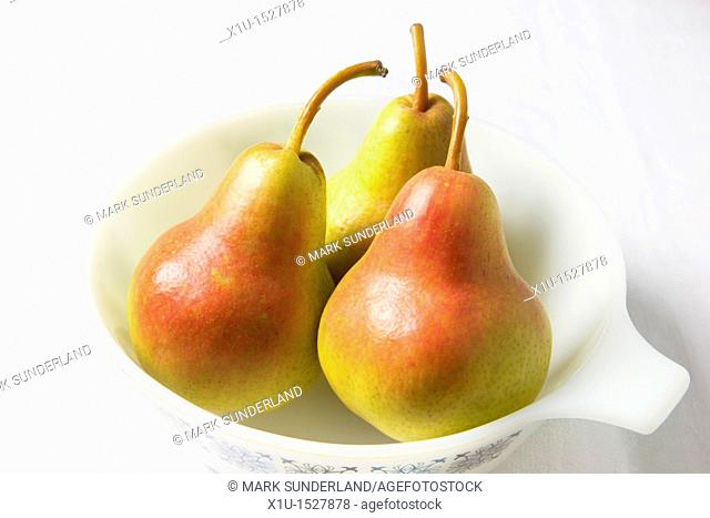 Three blush pears in a white dish