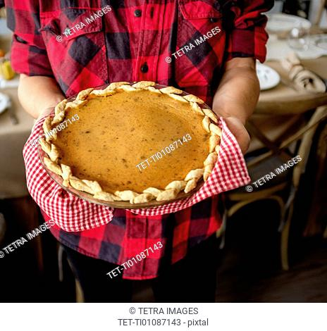 Woman holding baked pumpkin pie for Thanksgiving