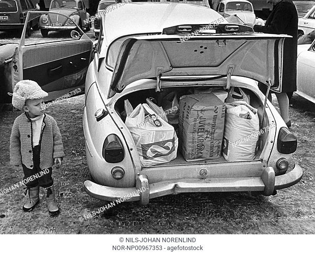 Rear of a car with a child standing aside