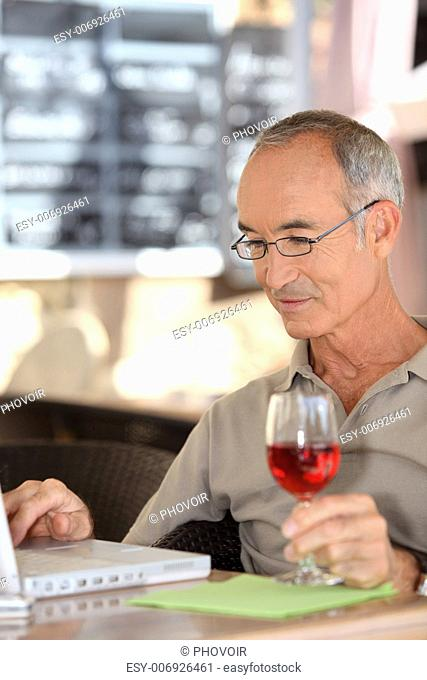 Grey haired man using laptop whilst drinking glass of wine