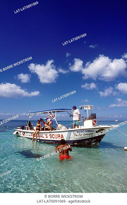 Dive boat. In shallow water. Man in water. Two women on deck