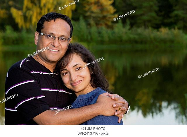 Portrait of a married couple in a park in autumn; Edmonton, Alberta, Canada