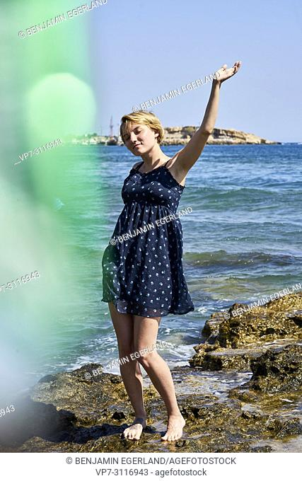 woman dancing at beach, sensual, enjoying warm summer breeze, in holiday destination Chersonissos, Crete, Greece