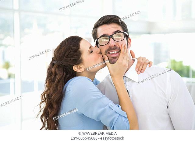 Portrait of a woman kissing her colleague
