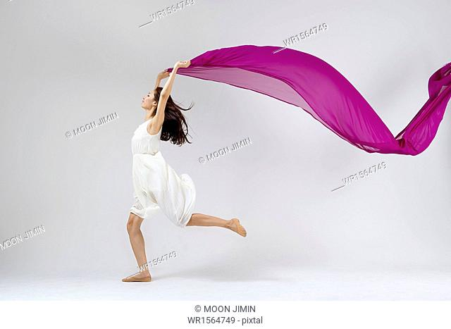 ballerina in white dress dancing with purple piece of cloth