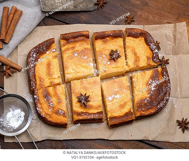 cut into pieces of a rectangular cake of cottage cheese and pumpkin on brown paper, top view