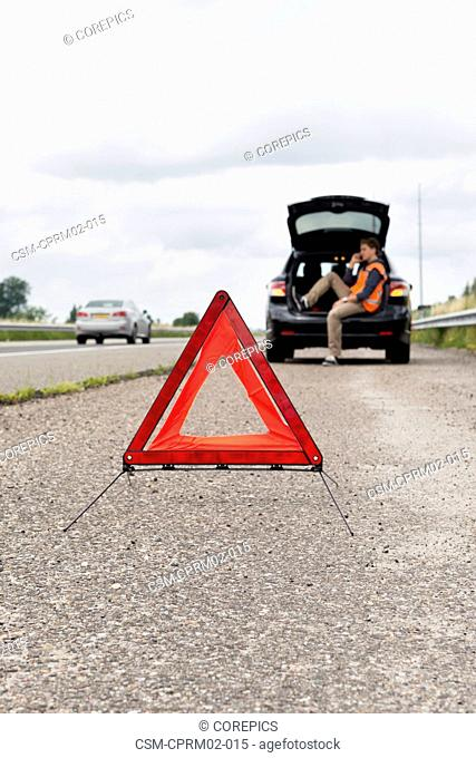 Warning triangle on the shoulder of a motorway behind a stalled car, with the owner and driver making a phone call, sitting in the booth of his vehicle