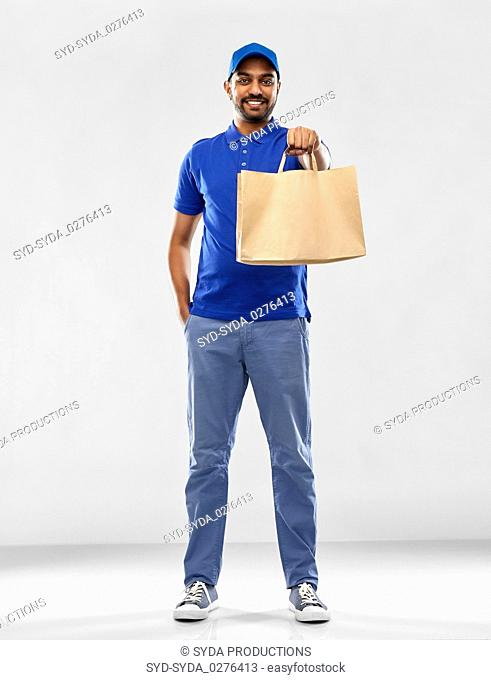 happy indian delivery man with food in paper bag