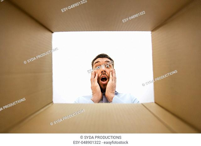 shocked man looking into open parcel box