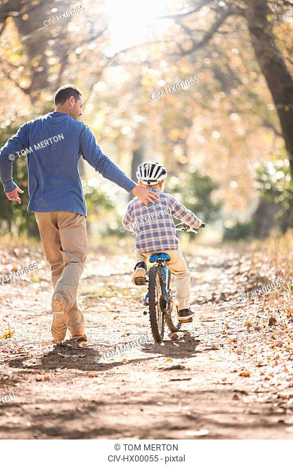 Father teaching son to ride bicycle on path in woods