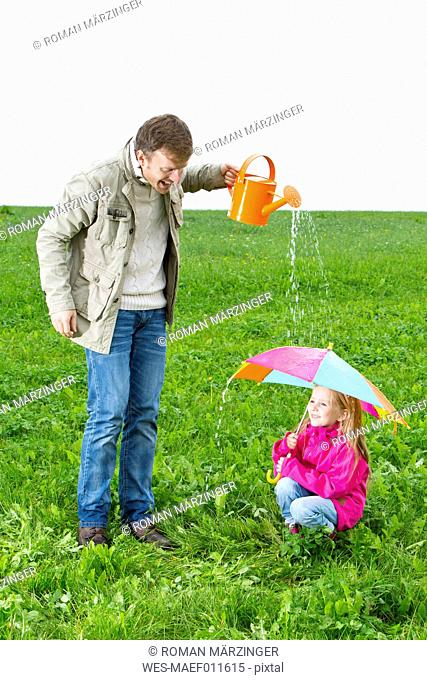 Father with watering can and daughter with umbrella on meadow