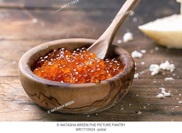Olive wood bowl of red caviar over old wooden table