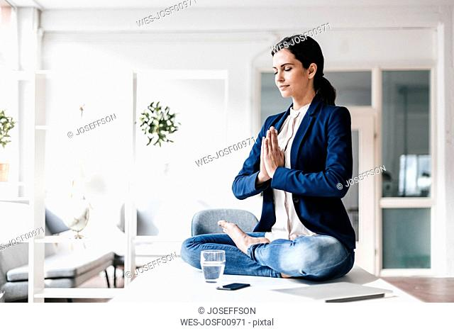 Businesswoman sitting on table meditating