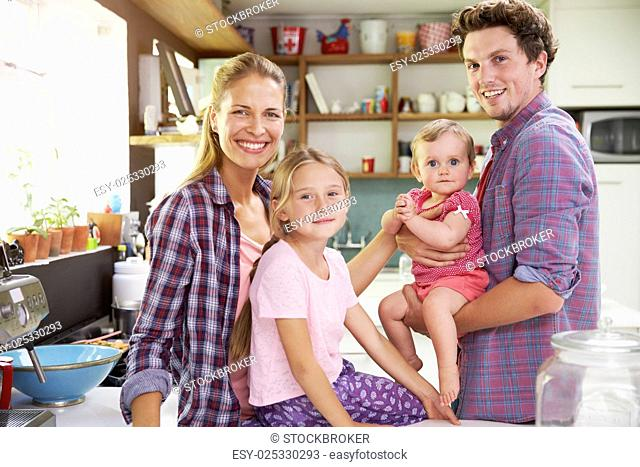 Portrait Of Family Cooking Meal In Kitchen Together