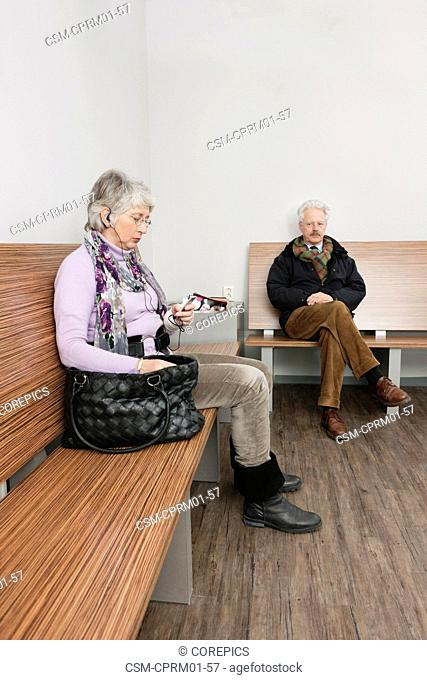 two elderly people sitting in a general practitioner's waiting room, reading various magazines and newspapers, one with an ipod in her hand