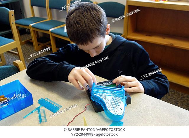 6th Grade Boy Working With Circuits, Wellsville, New York, USA
