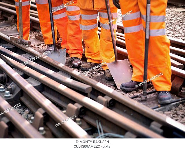 Railway maintenance workers standing with tools on track, low section