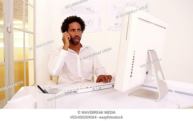 Angry businessman talking on phone at his desk